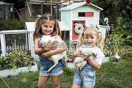dwie dziewczyny stojace przed kurnikiem w