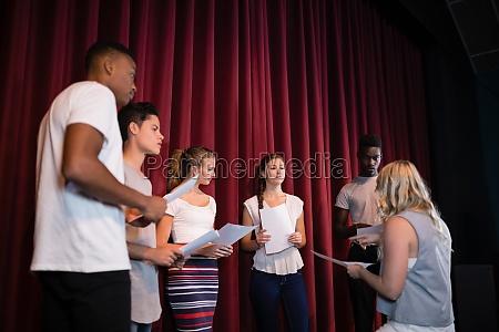 aktorzy czytajacy swoje scenariusze na scenie