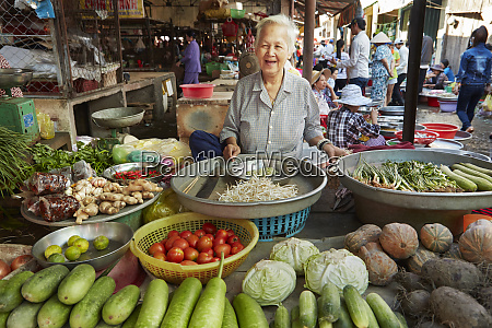 elderly woman with produce stall at