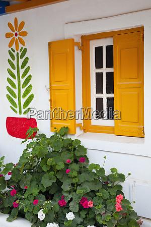grecja mykonos pomaranczowo zolte okno geraniums