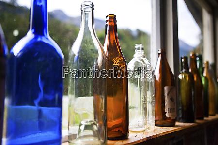 antique glass bottles line the windowsill