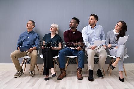 kandydaci siedzacy na krzesle czekaja na
