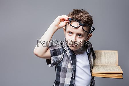inteligentny uczen w okularach z podrecznikiem