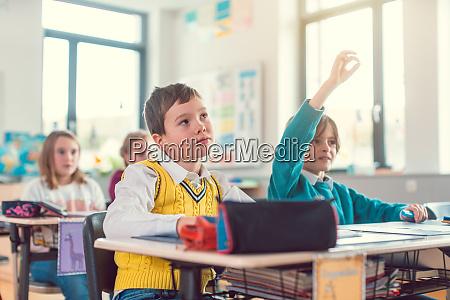 chlopiec uczen w klasie znajac odpowiedz