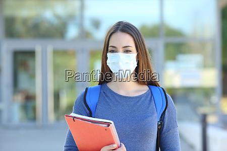 student w masce spaceru w kampusie