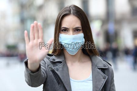 powazna dziewczyna robi znak stop z