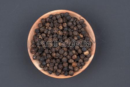 whole black peppercorns in a small
