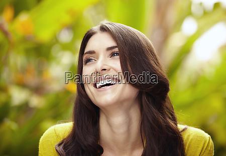 usmiechnieta kaukaska kobieta stojaca w lisciach