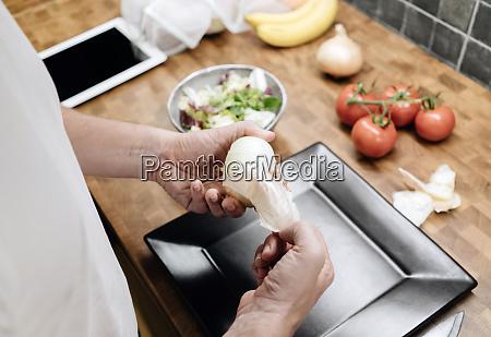 dojrzaly mezczyzna stojacy w kuchni obierania