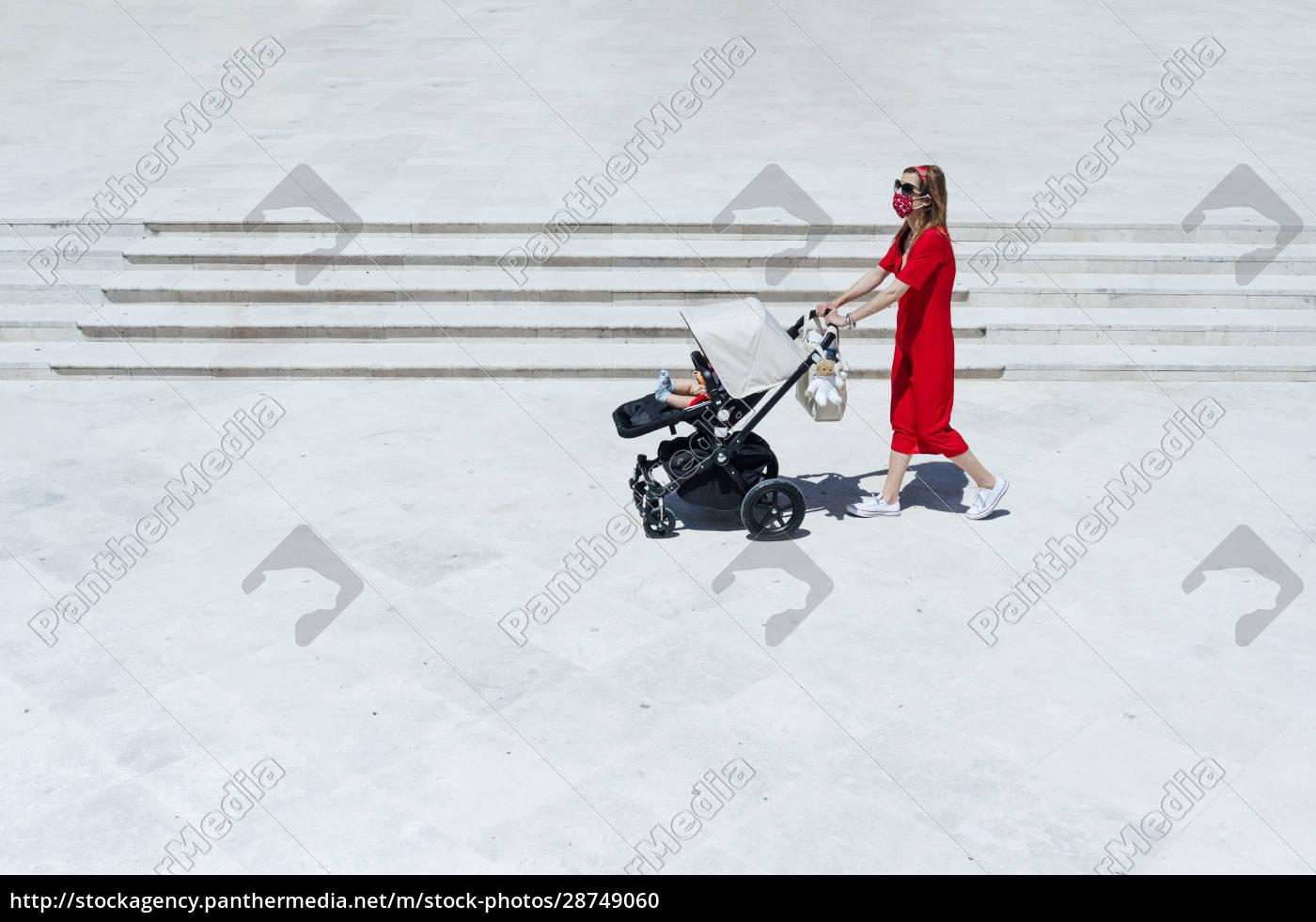 mother, wearing, mask, pushing, son, in - 28749060