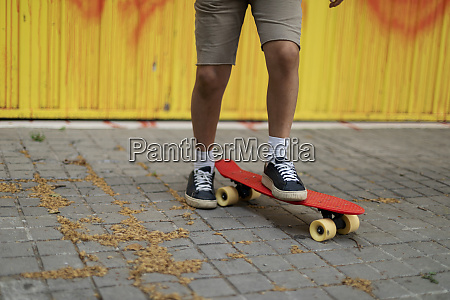nogi chlopca skateboarding na chodniku