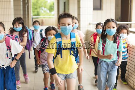 grupa dzieci noszacych maske z powrotem