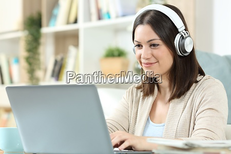 kobieta ze sluchawkami i laptopem w