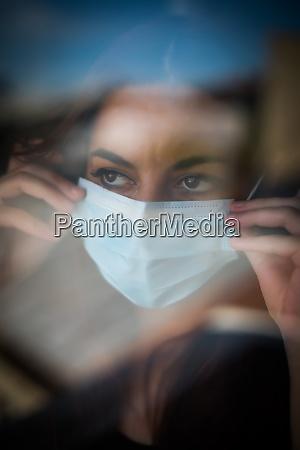 kobieta ubrana w maske chirurgiczna przez
