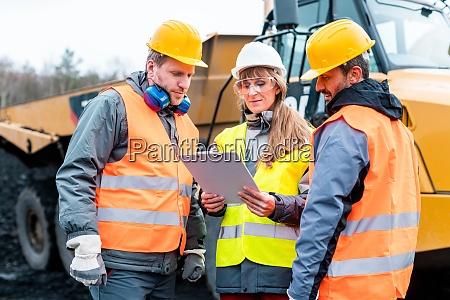 trzech pracownikow kamieniolomu dyskutuje przed ciezkimi