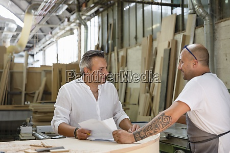 kierownik projektu rozmawia ze wspolpracownikiem stojac