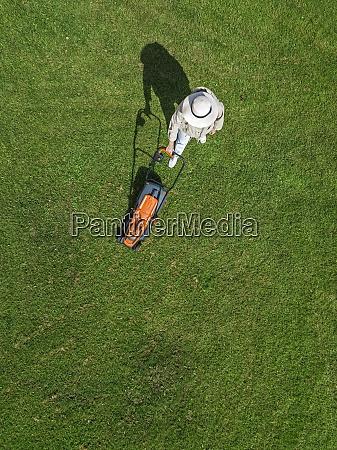 kobieta z kosiarka stojaca na trawie