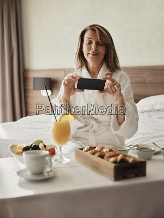 usmiechnieta blond starsza kobieta fotografujaca sniadanie