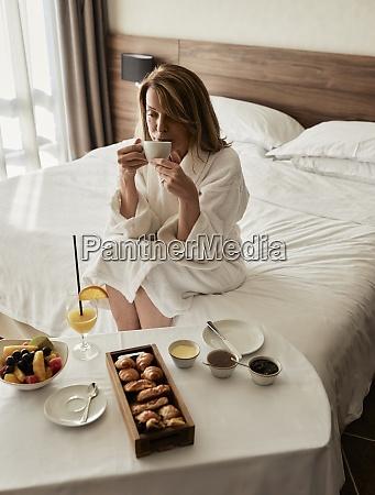 blond starsza kobieta pijaca kawe podczas