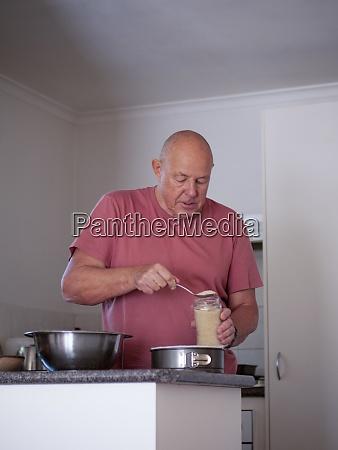 starszy mezczyzna przygotowuje skladniki na ciasto